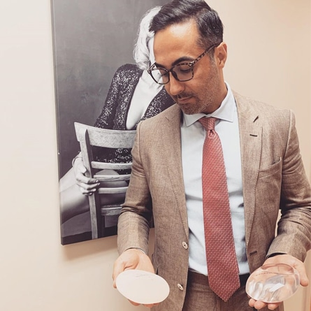 Dr. Sadeghi holding two different types of breast implants